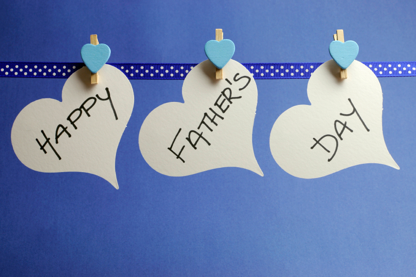 Happy Fathers Day message written on white heart tags hanging from polka dot ribbon with pegs on a line against a blue background.